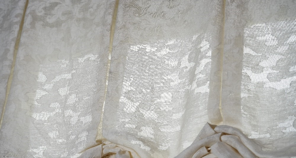 A pair of cream linen Roman blinds hung with black and white bobble tassels.142cm wide x 230cm long Image
