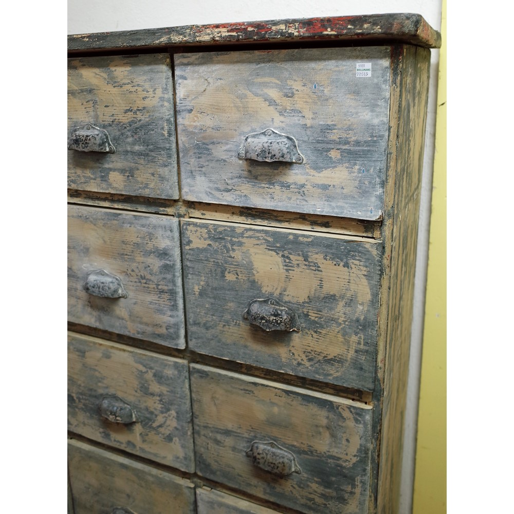 A distressed painted pine bank of four rows of four short drawers over one long drawer Image