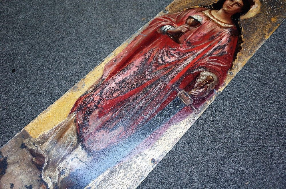 A polychrome painted tin panel depicting 'St Barbara', modelled holding a goblet and sword... Image