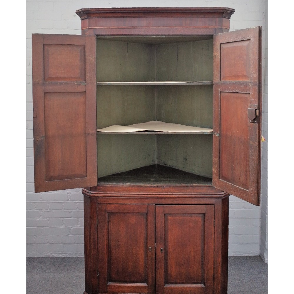 A mid-18th century oak double height floor standing corner cupboard with two pairs of panel doors... Image