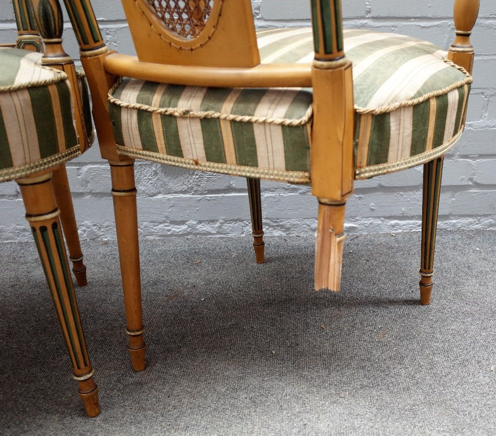 A set of six Sheraton revival polychrome painted open armchairs, with cane oval panel back and... Image