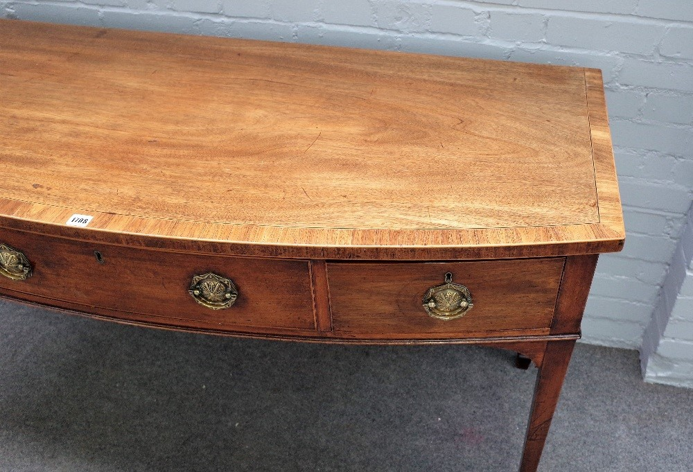 A George III inlaid mahogany bow front serving table, with three frieze drawers on tapering... Image