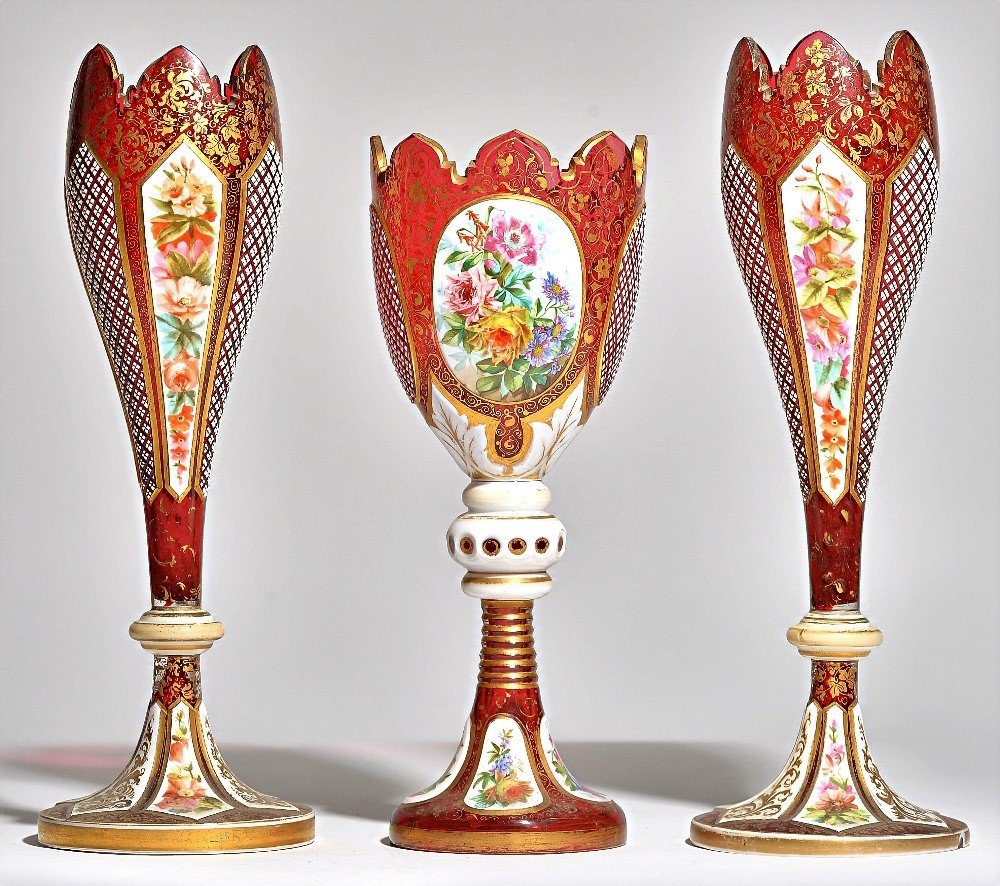 A pair of late 19th century Bohemian ruby glass vases with foliate painted white enamel overlay... Image