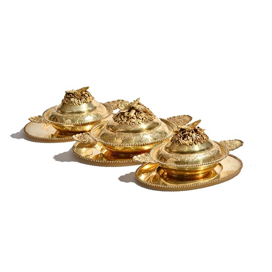 A set of three silver gilt lidded dishes and stands, the larger dish decorated with birds,... Image