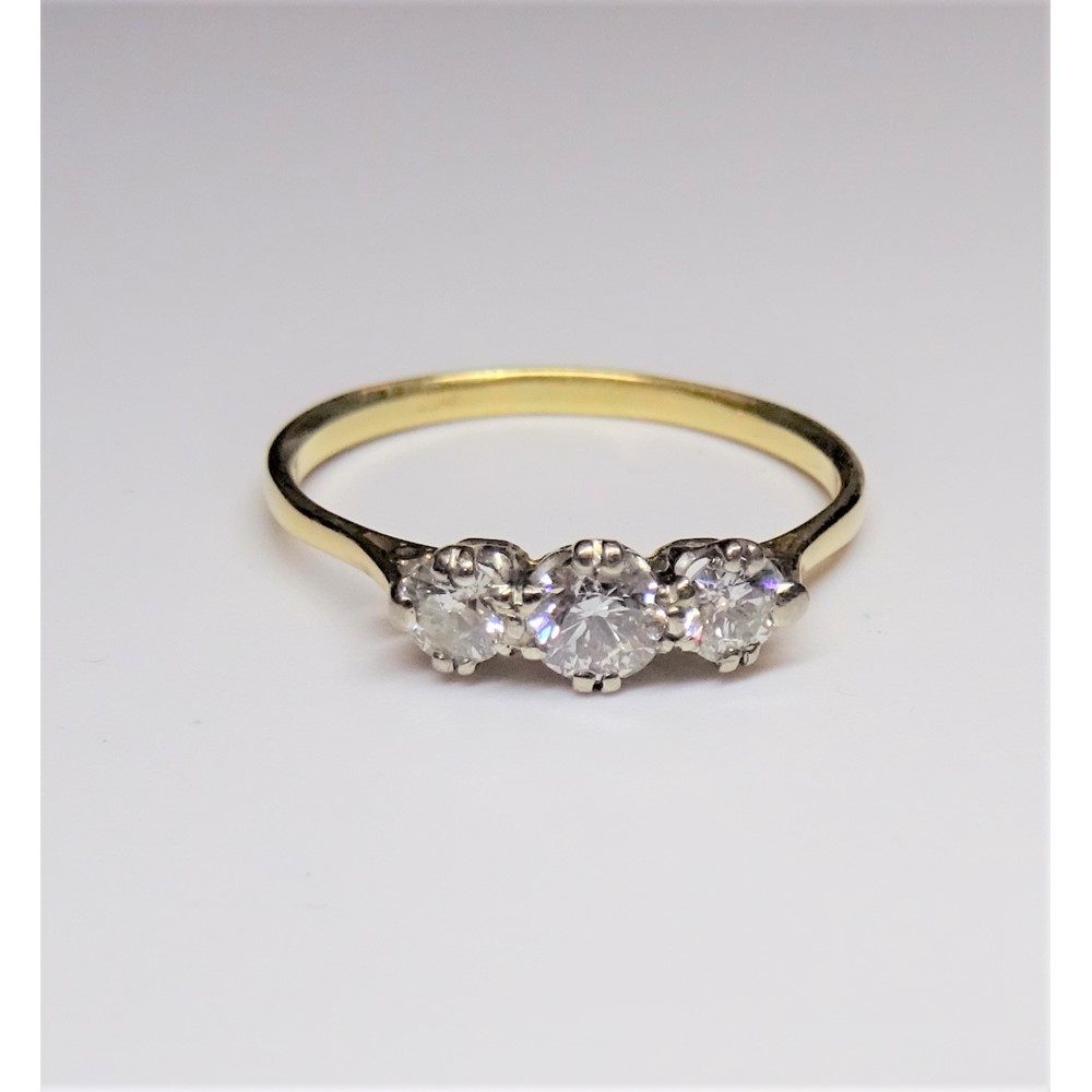 A gold and diamond set three stone ring, claw set with a row of circular cut diamonds and with... Image