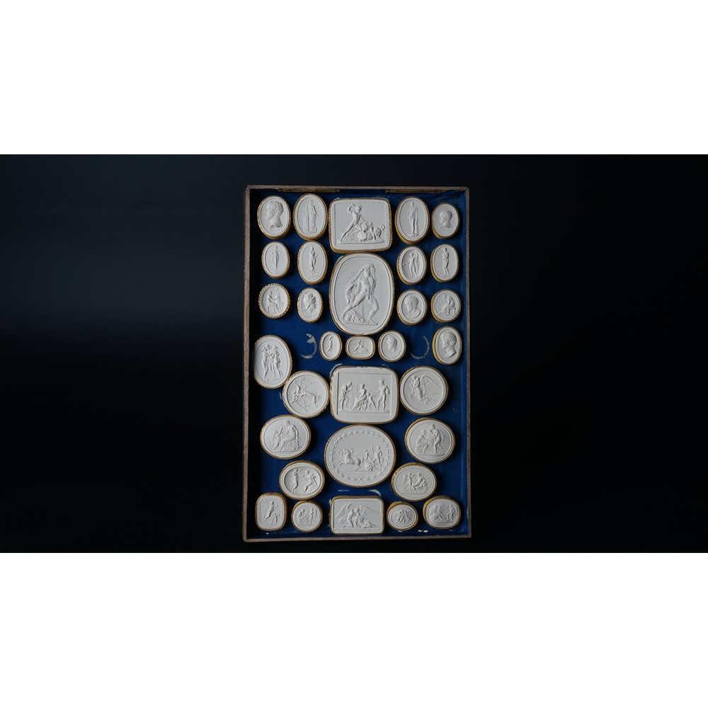 A quantity of plaster intaglios 'Casts From The Antique' housed in two cases, each comprising... Image