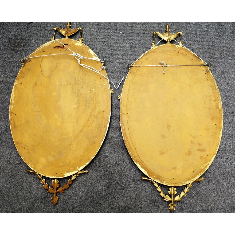 A pair of 20th century gilt framed oval mirrors with urn and floral swags, 40cm wide x 73cm high. Image