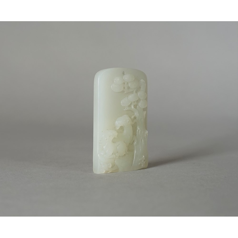 A Chinese white jade rectangular pendant, Qing Dynasty, carved with two goats beneath a pine... Image