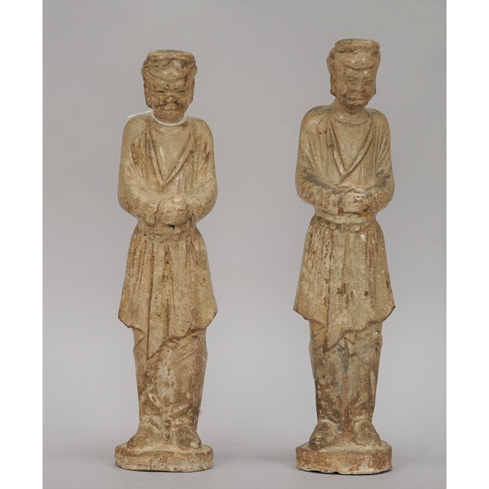 A pair of Chinese pottery figures of grooms, Sui/Tang dynasty or later, each male standing with... Image