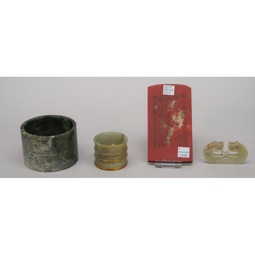 A Chinese archaistic spinach jade cylinder, carved with panels of taotie masks, 6cm. high; also a... Image