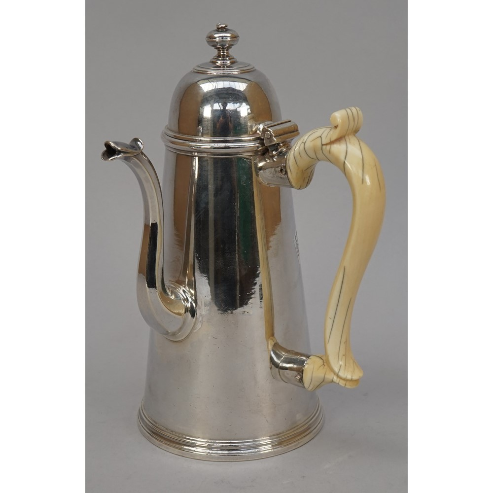A George I Britannia Standard silver coffee pot, of tapered cylindrical form, with a hinged domed... Image