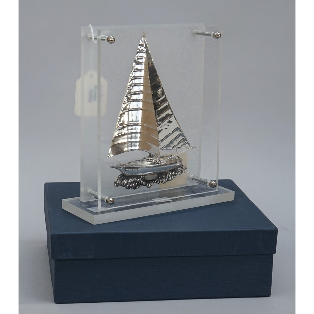 A silver model of a Greek yacht, in sail with rigging, displayed in a perspex stand, detailed... Image