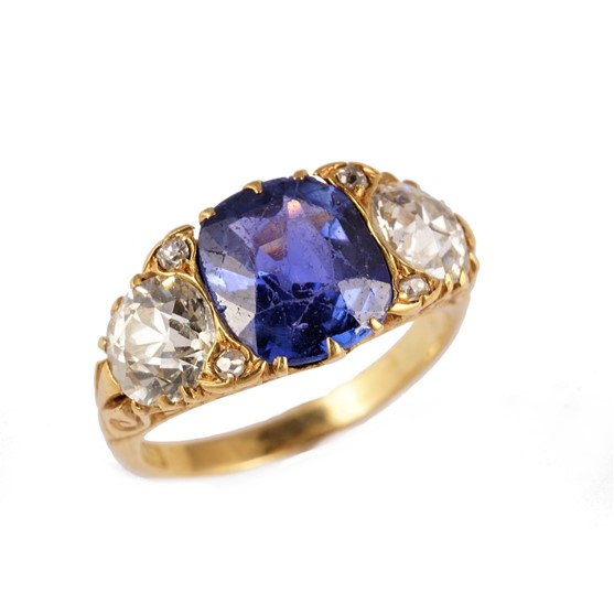 A gold, Ceylon sapphire and diamond ring, claw set with the cushion shaped Ceylon sapphire at the... Image