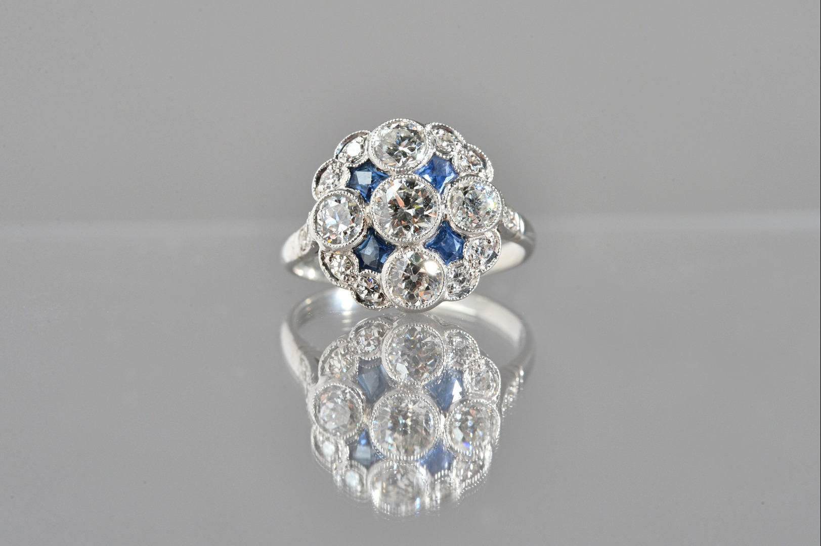 A diamond and sapphire cluster ring,... Image