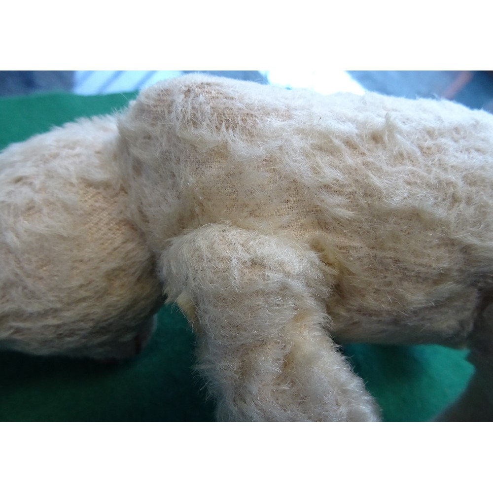 An early 20th century Steiff style teddy bear with plush golden fur, glass eyes, stitched snout,... Image