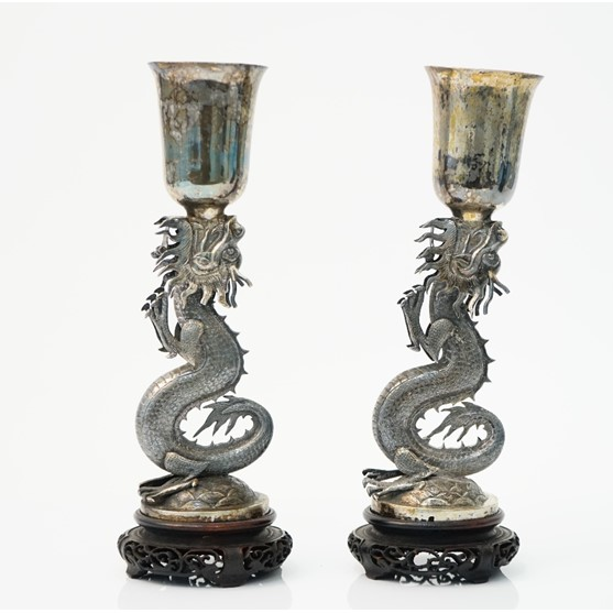 A pair of Chinese vases, each supported by an open mouthed dragon, raised on a circular base,... Image