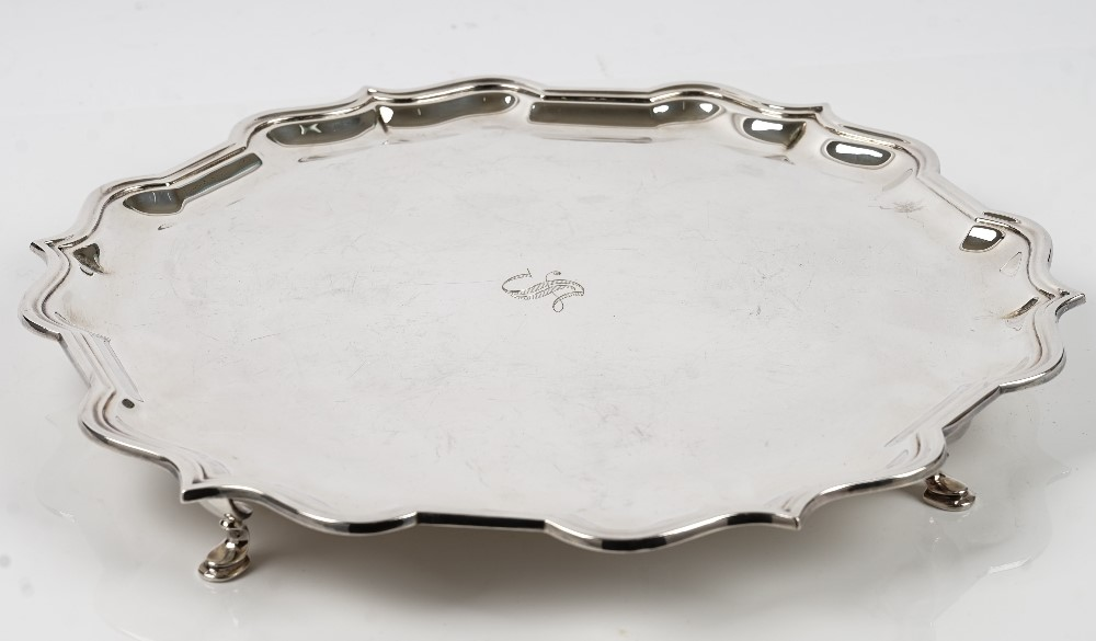 A silver salver of shaped circular form, having a piecrust rim in the Chippendale style raised on... Image