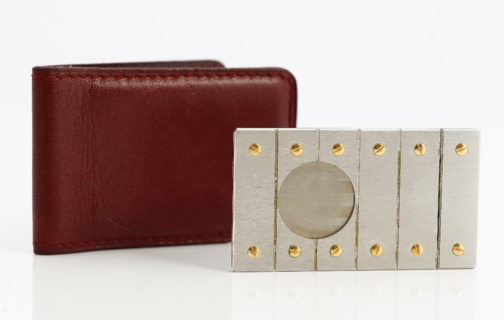 A Must de Cartier steel and gold sliding cigar cutter, of rectangular form, decorated with screw... Image