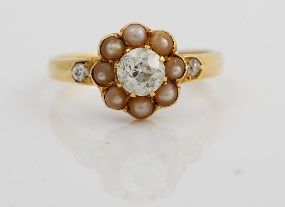 A late Victorian gold, diamond and seed pearl ring, of cluster design, the central circular cut... Image