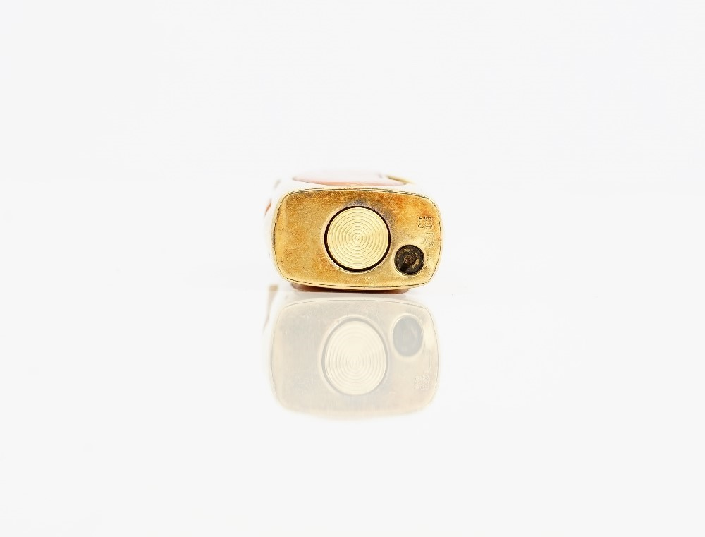 A gold mounted coral curved rectangular cased gas lighter, detailed 750, the hinged cover and the... Image