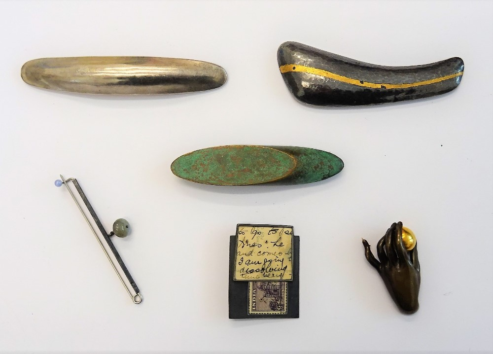 A collection of six modern studio brooches, including a bronze brooch modelled as a hand holding... Image