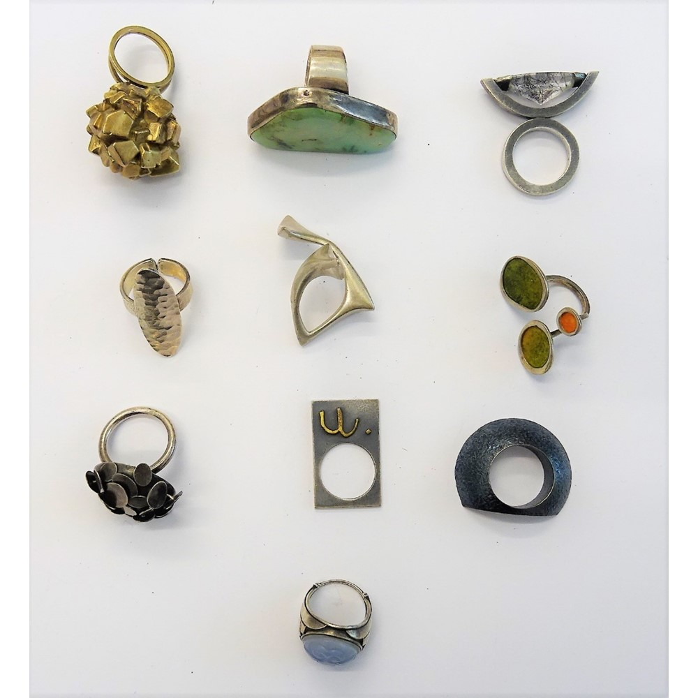 A collection of ten mostly silver rings, in a variety of modern abstract designs, including one... Image