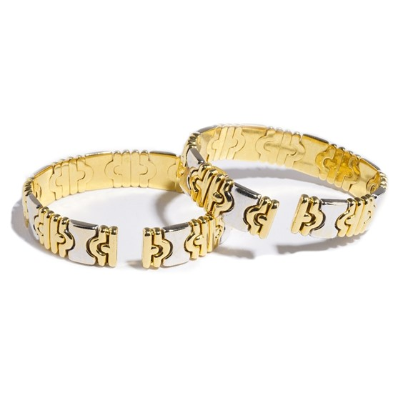 A pair of Italian two colour gold and diamond set sprung bangles, the front of each with diamond... Image