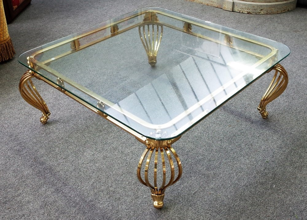 A 20th century coffee table, the rounded square glass top on four lacquered brass open slatted... Image