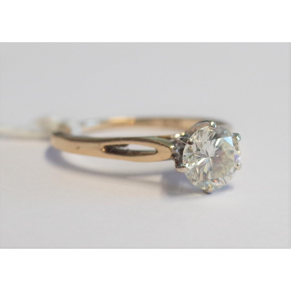 A gold and diamond single stone ring, claw set with a circular cut diamond, detailed 14 K, ring... Image
