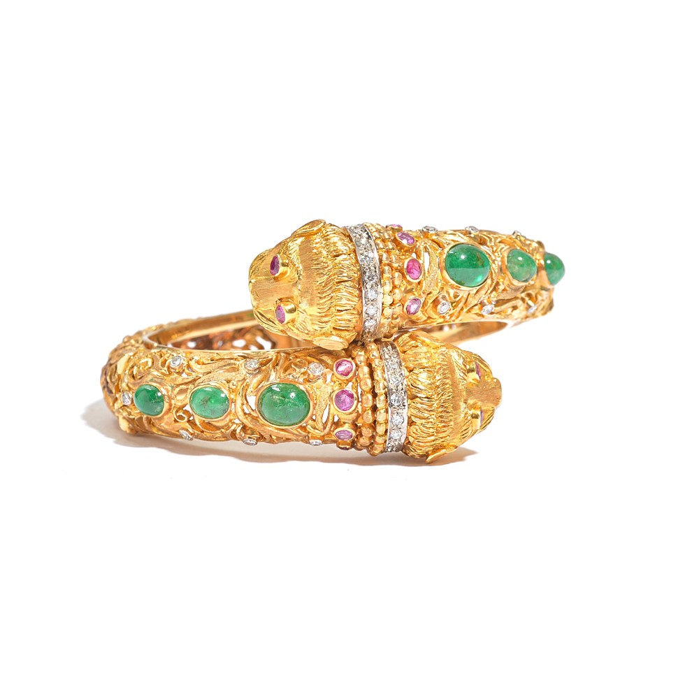 An emerald, ruby and diamond hinged bangle by Ilias Lalaounis, the hinged open work bangle of... Image