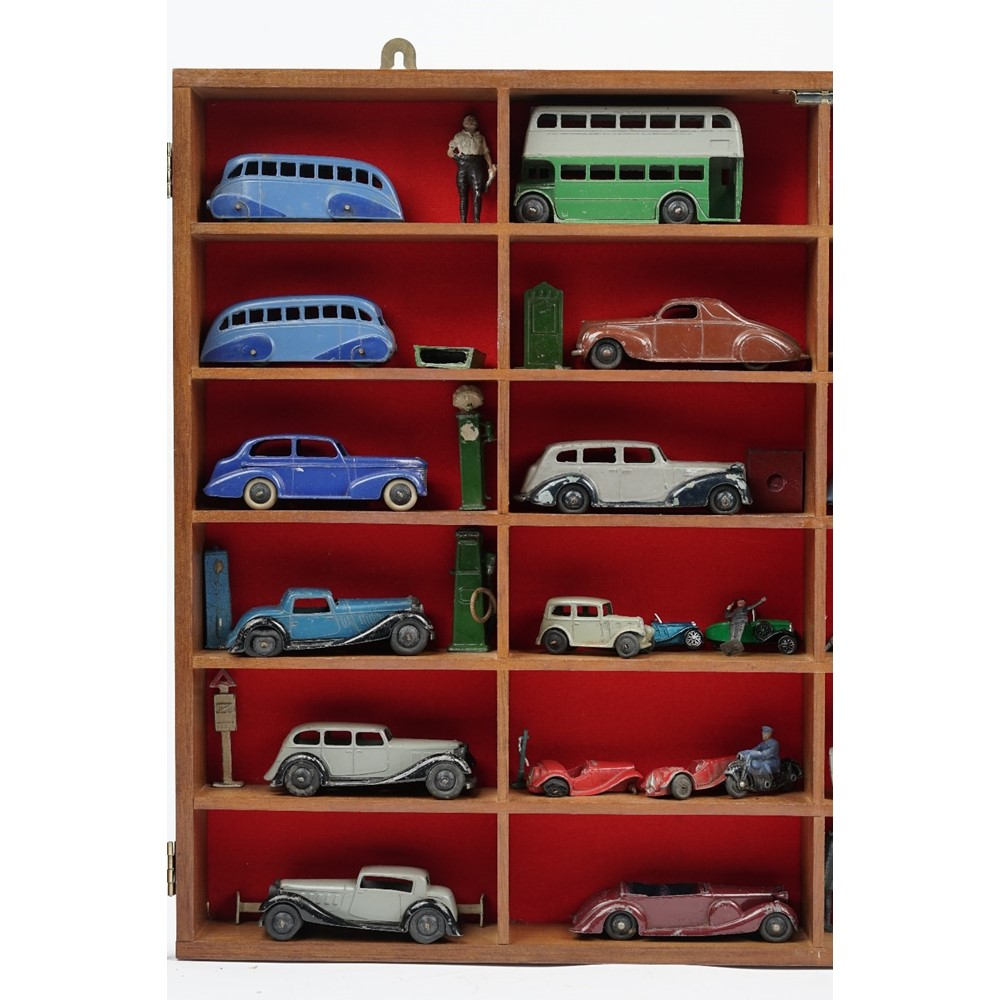 Twenty-four pre-war Dinky die-cast vehicles and related items in a glazed mahogany wall cabinet,... Image