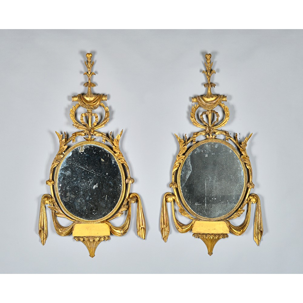 A pair of George III framed wall mirrors, each with ribbon and swag moulding about the oval... Image
