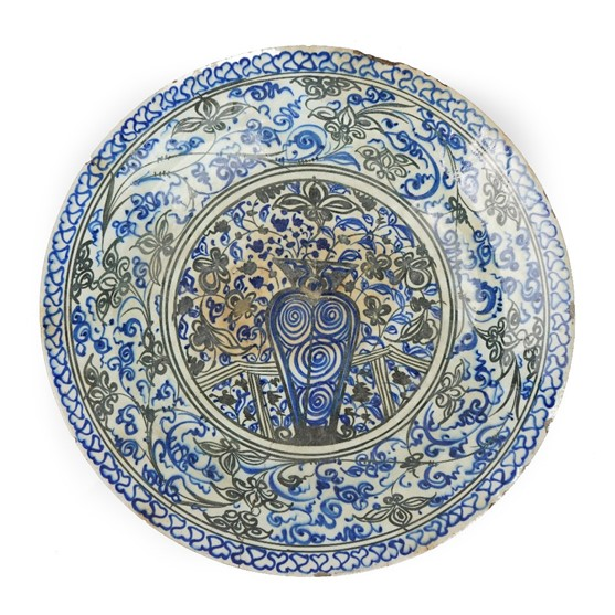 A large Safavid blue and black porcelain dish, first half 17th century, painted with a central... Image