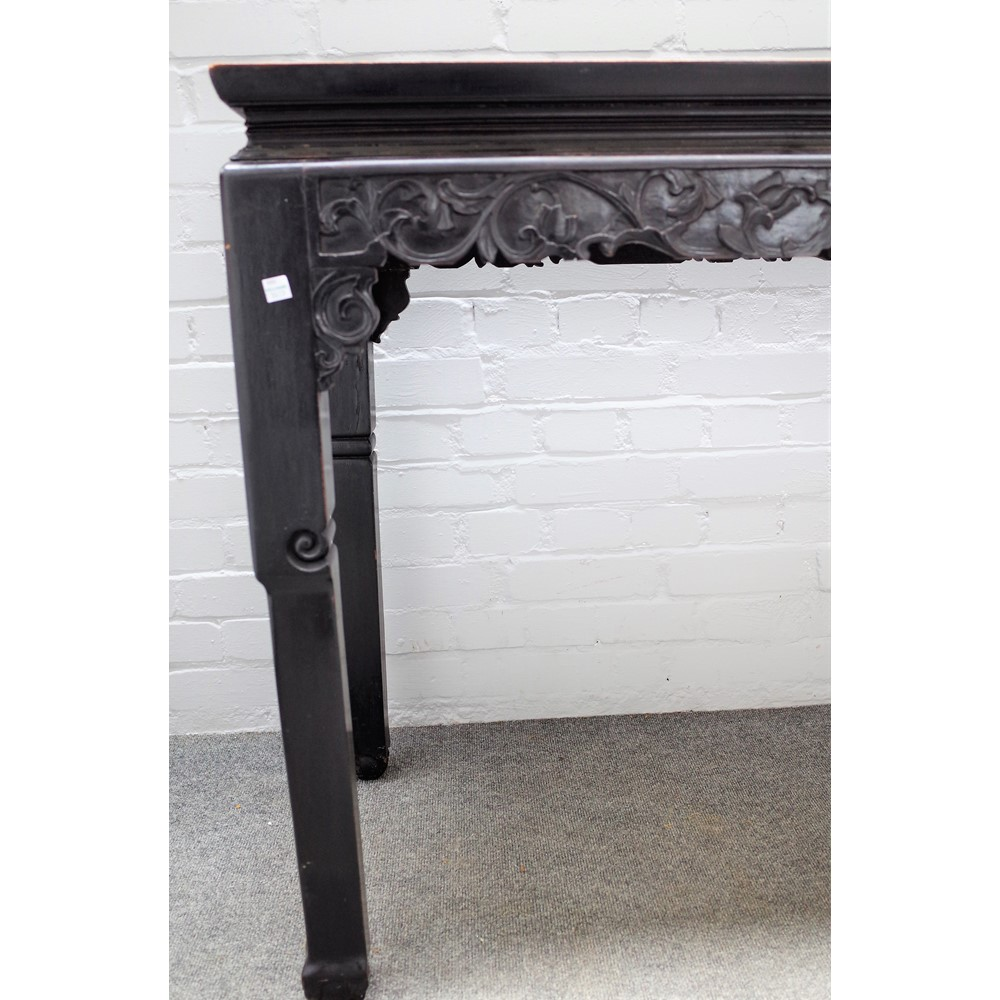 A 19th century Chinese hardwood console table with floral carved frieze on instepped block... Image