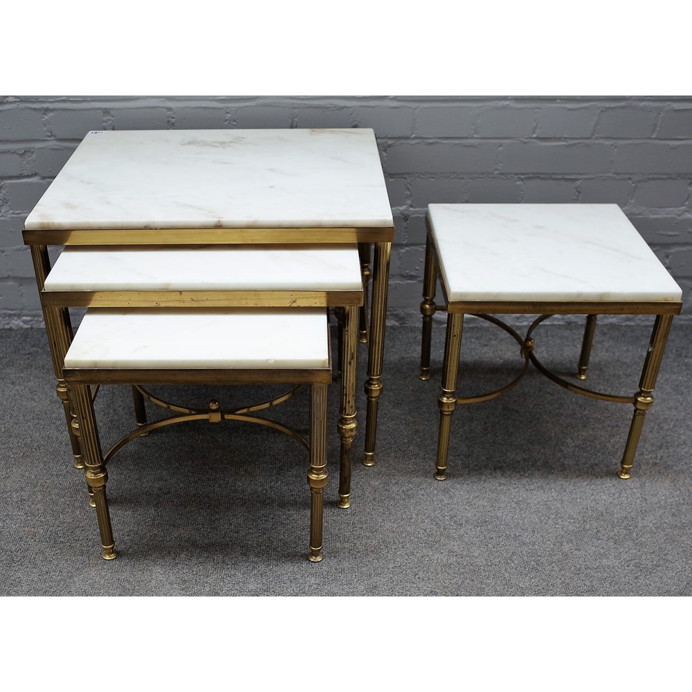 A nest of three 20th century lacquered brass occasional tables with marble inset tops on reeded... Image