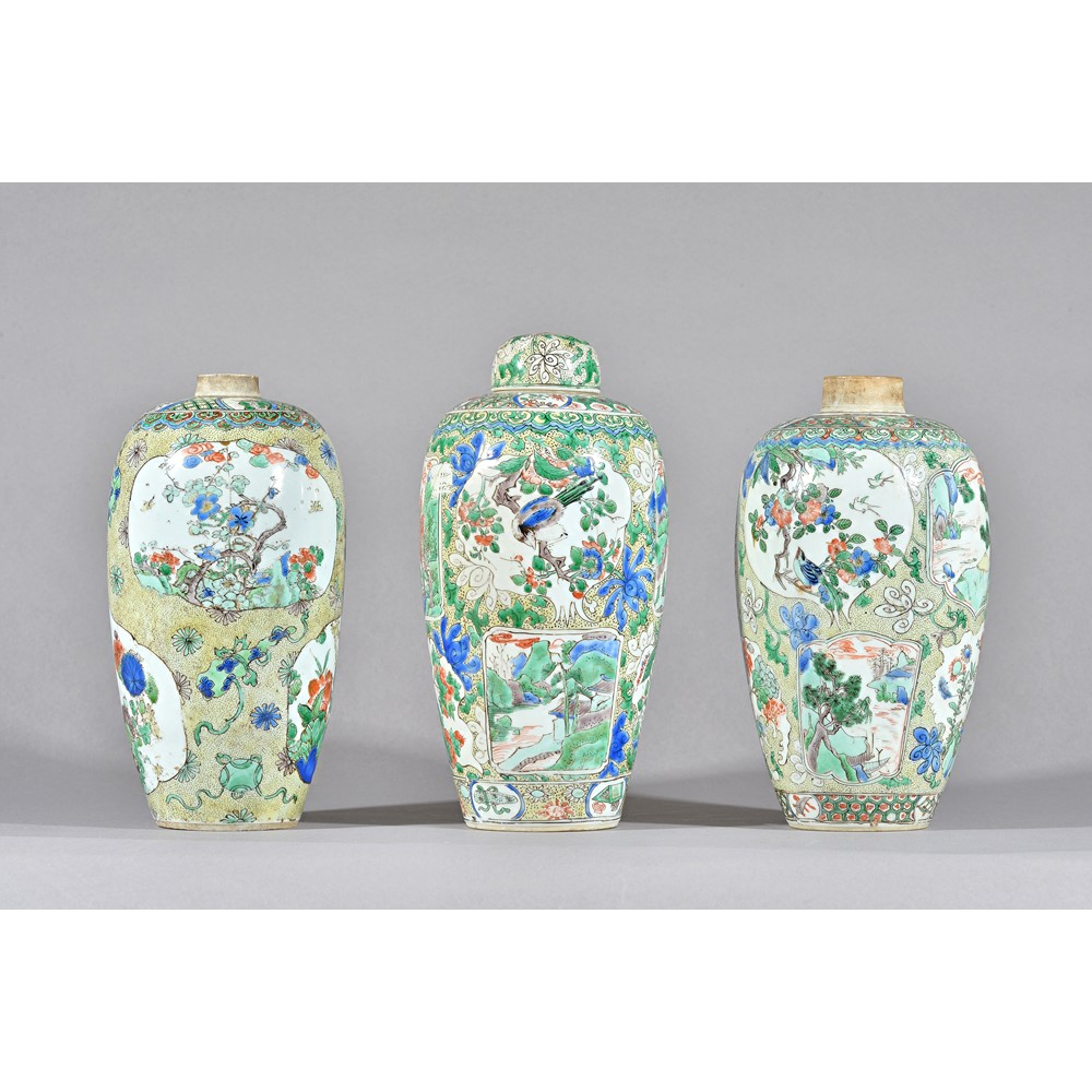 Three Chinese famille-verte ovoid vases and a cover, probably Kangxi, painted with shaped panels... Image