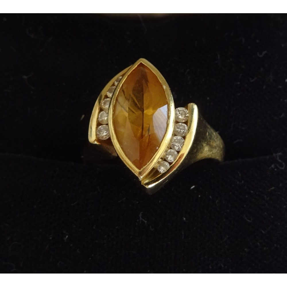 An 18ct gold, citrine and diamond ring, mounted with the marquise shaped citrine between two rows... Image