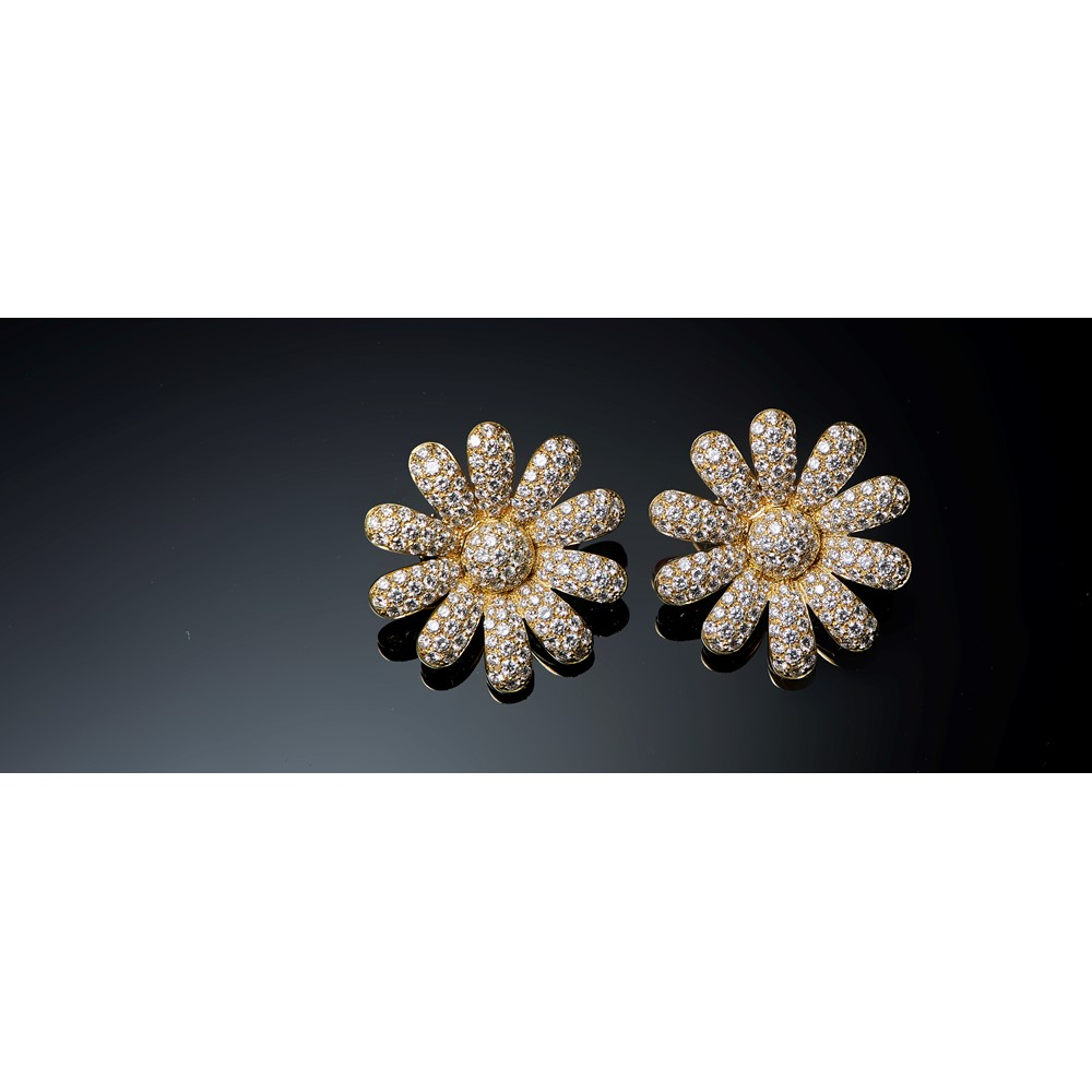 A pair of gold and diamond set earclips, each designed as a flowerhead, mounted with circular cut... Image