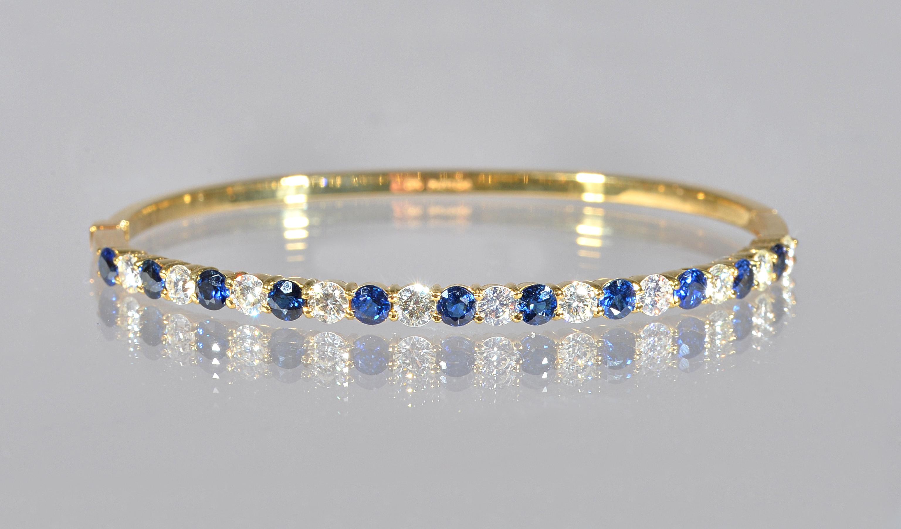 An 18ct gold, sapphire and diamond oval hinged bangle, claw set with a row of circular cut... Image