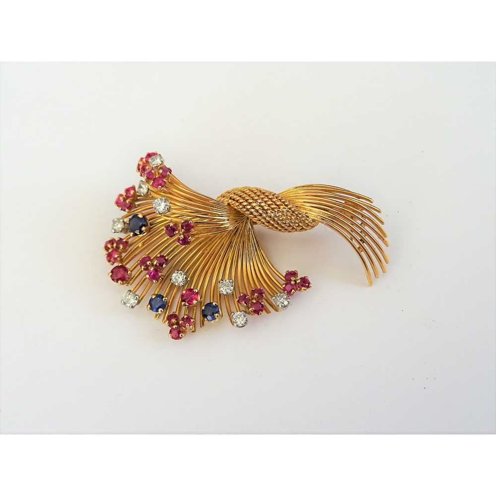 A gold, diamond, ruby and sapphire set brooch, designed as a wirework spray, claw set with... Image