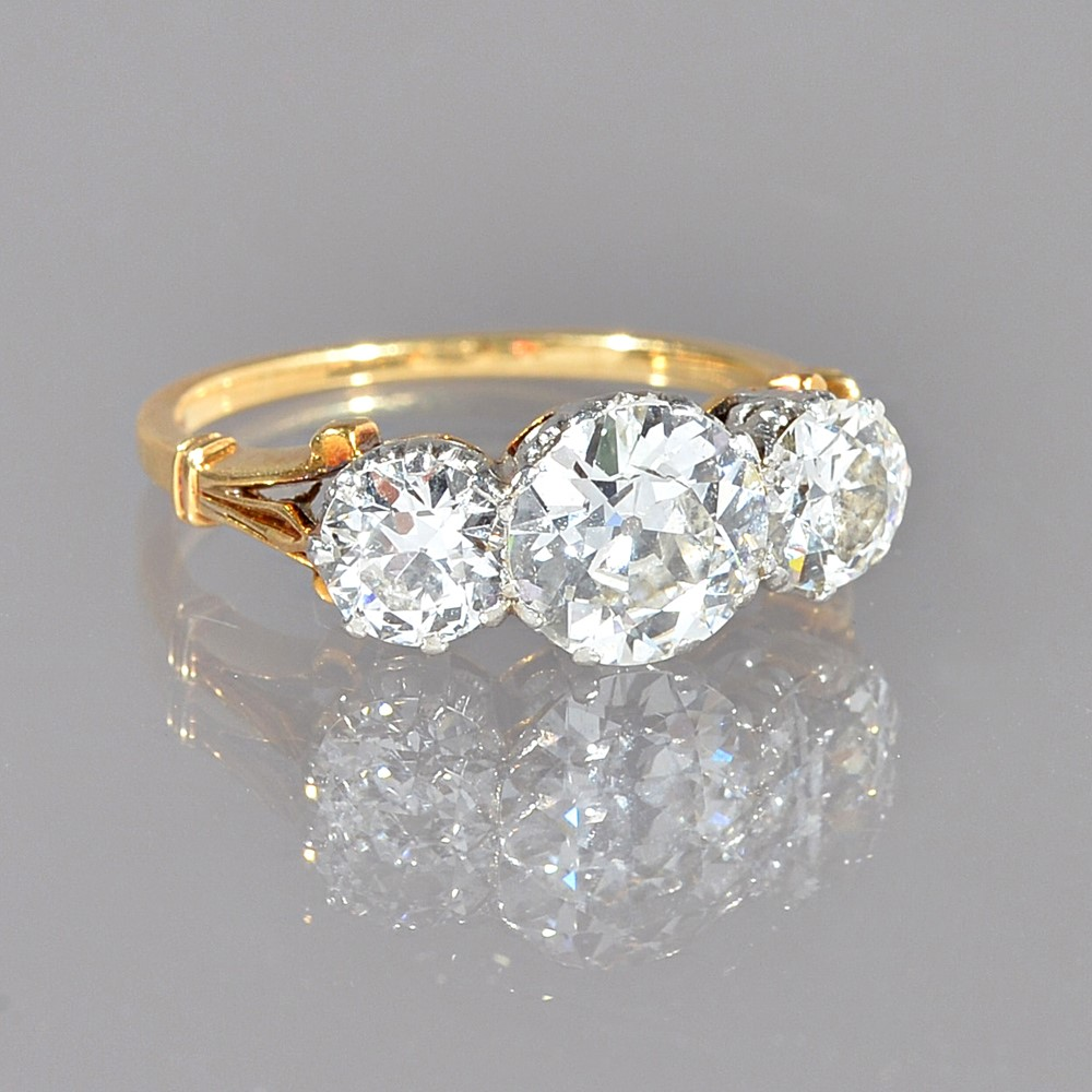 A gold and diamond three stone ring, claw set with the principal cushion shaped diamond to the... Image