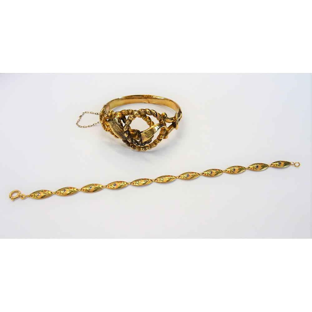 A gold oval hinged bangle, the front in an entwined design, on a snap clasp and a gold and... Image