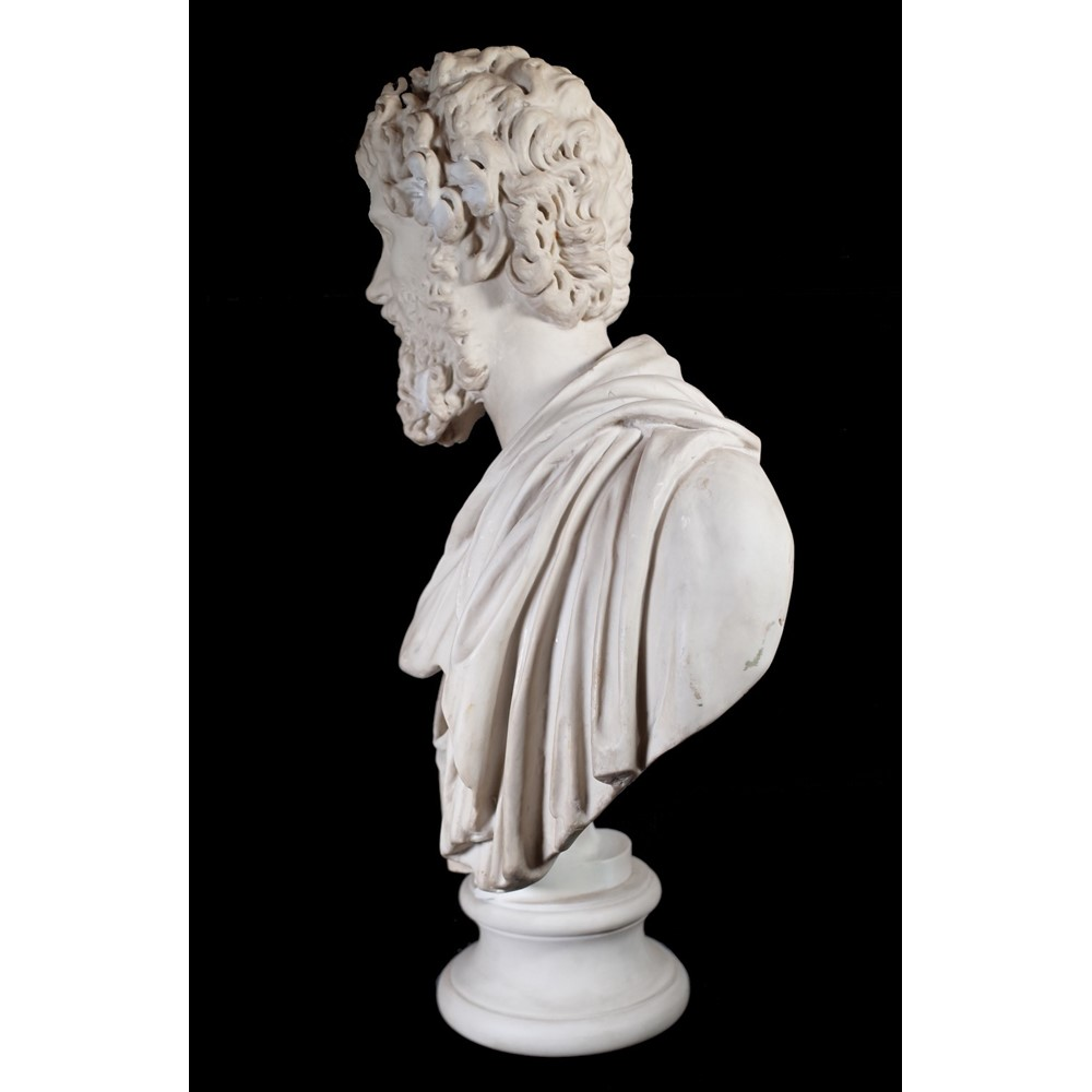 After the Antique; a modern resin bust depicting a man in Roman clothing, on turned socle, 79cm... Image