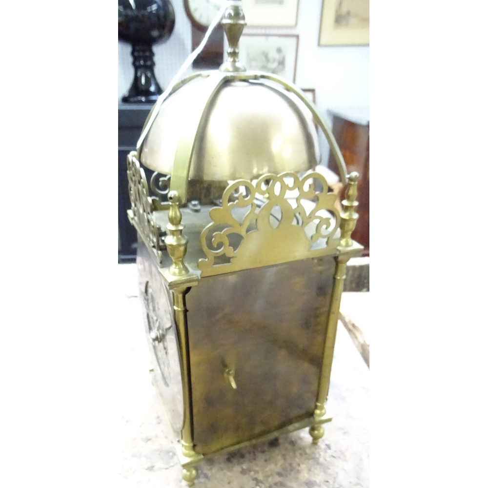 A BRASS QUARTER-STRIKING LANTERN CLOCKCirca 1910The case of typical form, surmounted by a bell... Image