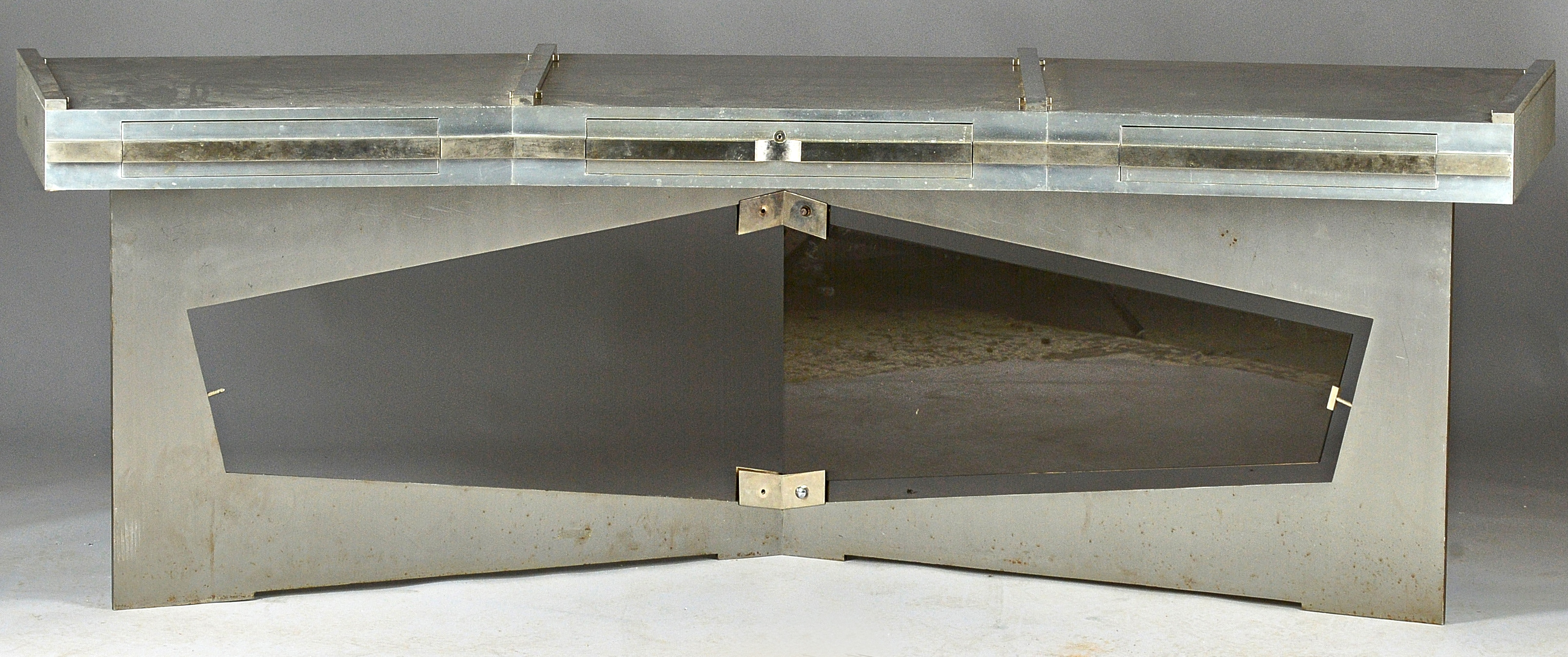 A mid-20th century Continental steel and aluminum angular bowfront desk, the angular top (lacking... Image