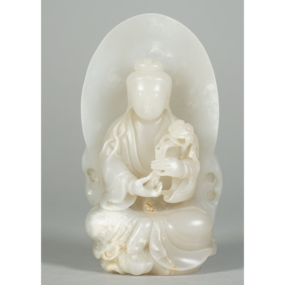 A Chinese white jade figure of Guanyin, Qing dynasty, the goddess seated before an oval mandorla,... Image