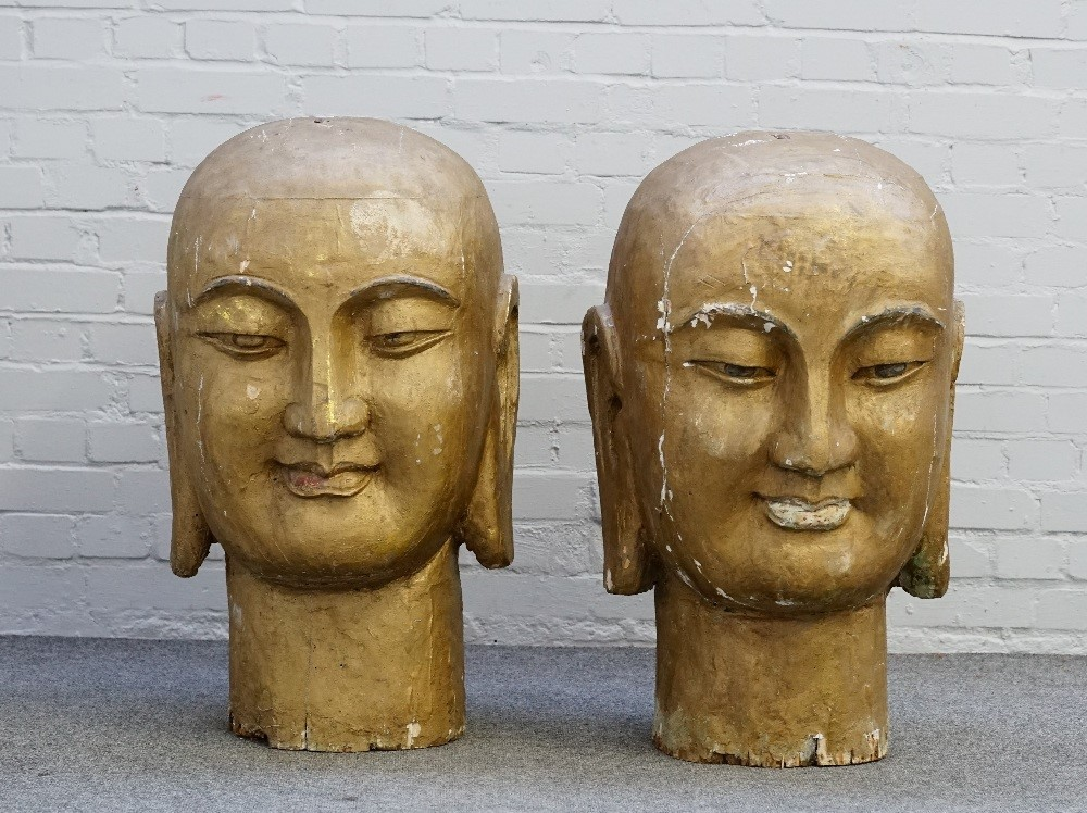 A pair of large gold painted Buddhistic style heads with elongated ears, each 82cm high. Image