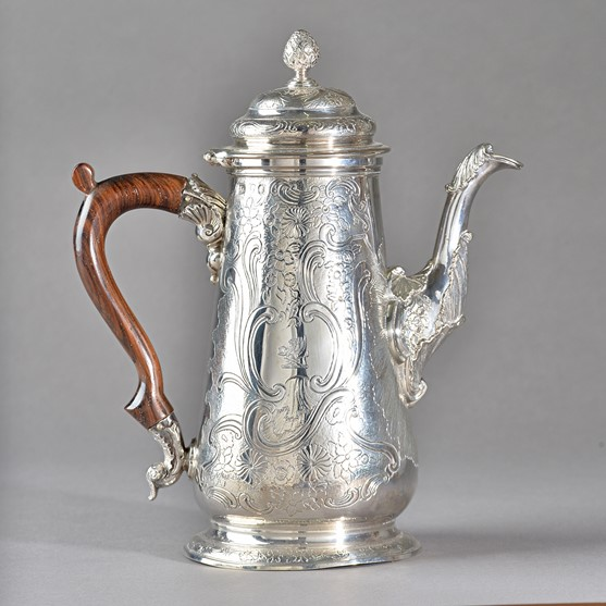 A George II silver coffee pot, of tapered cylindrical form, with later floral, foliate and scroll... Image