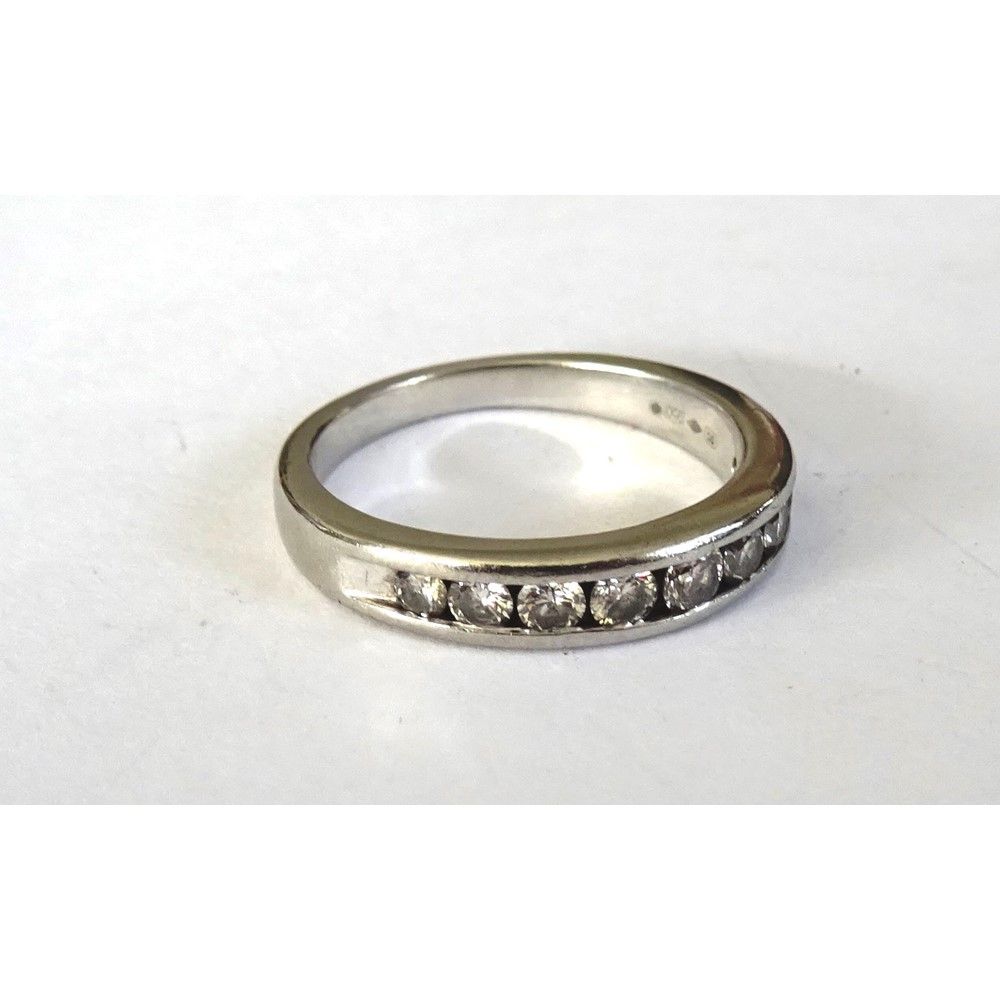 A platinum and diamond half hoop eternity ring, channel set with a row of nine circular cut... Image