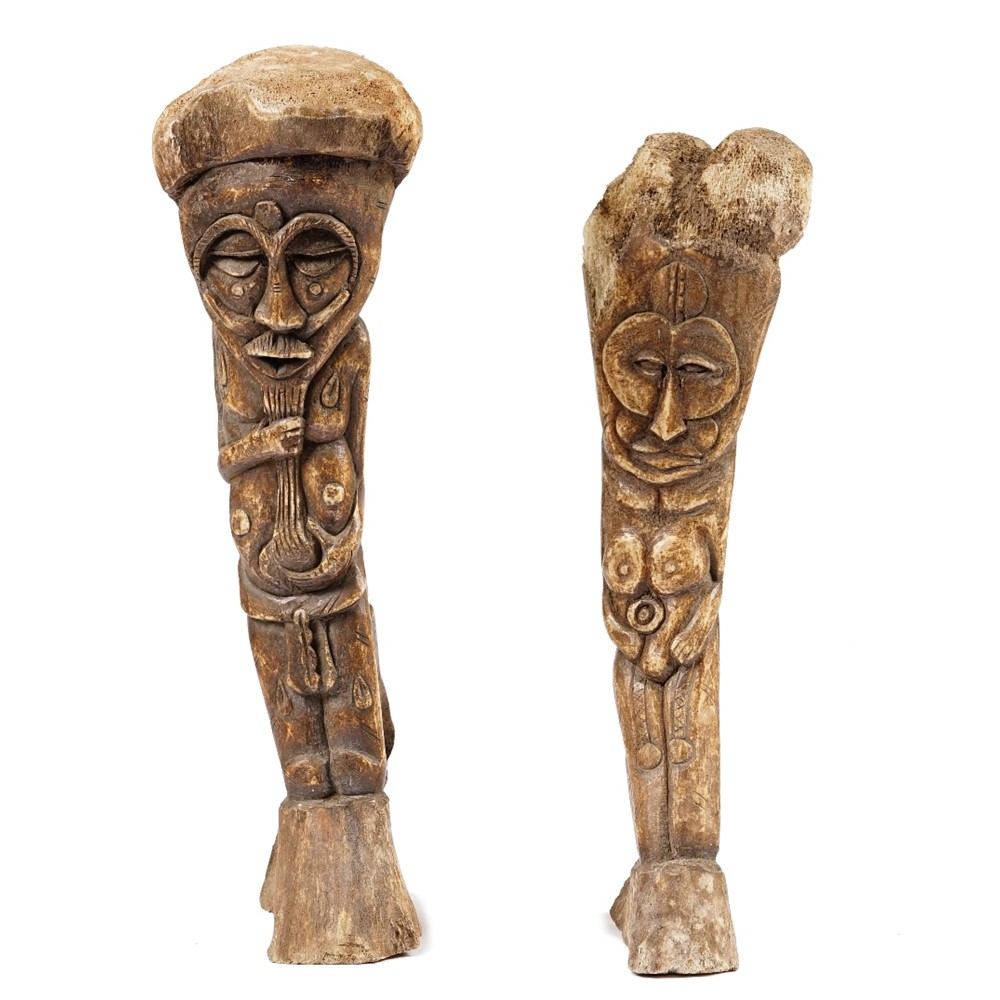 An Inuit whale bone carving of a tribal figure, 56cm high, together with another smaller example.... Image